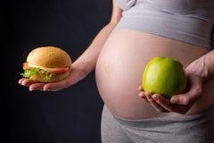 Живот беременной женщины держа плиту с старьем и здоровой едой Выбор концепции диеты во время беременности Стоковые Фотографии RF