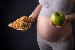 Живот беременной женщины держа плиту с старьем и здоровой едой Выбор концепции диеты во время беременности Стоковая Фотография