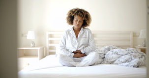 живот девушки кровати боли сидя Стоковые Фото