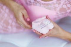 Живот ` s беременной женщины с розовыми добычами младенца Стоковая Фотография