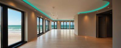 Живущая комната в современной квартире, вид на море стоковое изображение