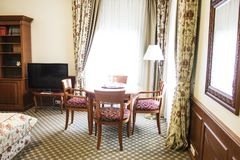 Живущая комната пожилой персоны с bookcase, античной таблицей Стоковые Фото