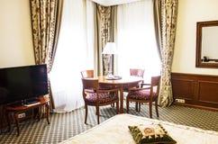 Живущая комната пожилой персоны с bookcase, античной таблицей Стоковая Фотография