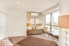 Живущая комната с видом на город около стеклянных окон Стоковая Фотография