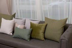 Живущая комната с зелеными валиками подушки на софе Стоковая Фотография