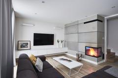 Живущая комната с камином и белыми конкретными коричневыми стенами стоковое изображение