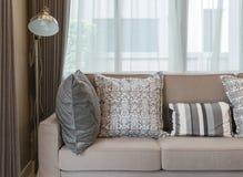 Живущая комната с коричневой софой и серым цветом сделала по образцу подушки дома Стоковые Изображения