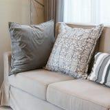 Живущая комната с коричневой софой и серым цветом сделала по образцу подушки дома Стоковое фото RF