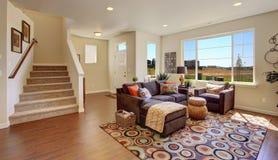 Живущая комната с коричневым креслом и жизнерадостным половиком стоковое изображение rf