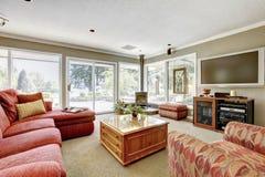 Живущая комната с красной софой, бежевой. Стоковые Фото