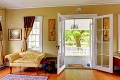 Живущая комната с открыть дверями к парадному крыльцу. Романтичная классика. Стоковая Фотография RF
