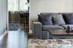 Живущая комната с черными софой и деревянным столом Стоковое Изображение RF