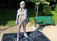 Живущая статуя - маленькая девочка с куклой Стоковая Фотография