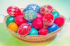 Живые покрашенные пасхальные яйца в коричневой корзине, предпосылка градиента, конец вверх Стоковое Фото