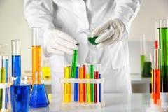 Жидкость ассистента лаборатории лить в пробирку над таблицей стоковое фото rf