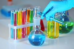 Жидкость работника лаборатории лить от пробирки в склянку на таблице, крупном плане стоковая фотография