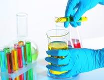 Жидкость работника лаборатории лить от пробирки в beaker на светлой предпосылке, крупном плане стоковое изображение