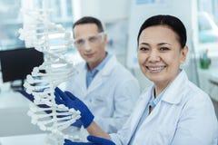 Жизнерадостная азиатская женщина держа модель дна в лаборатории Стоковое Фото