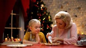 Жизнерадостная бабушка и девушка украшая печенья для рождественской вечеринки, счастливые праздники стоковое изображение