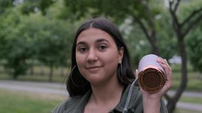 Жизнерадостная девушка брюнета с длинными волосами танцует в парке к музыке пока проводящ портативного диктора в ее руке сток-видео