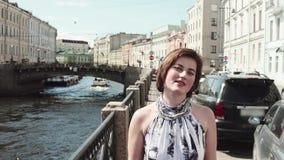 Жизнерадостная девушка в запятнанном платье поет вдоль реки в старом центре города видеоматериал