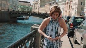 Жизнерадостная девушка в запятнанном платье поет на обваловке в старом центре города видеоматериал