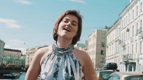 Жизнерадостная девушка в запятнанном платье поет на обваловке в старом городском центре сток-видео