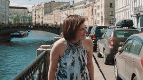Жизнерадостная девушка в запятнанном платье смеется над на обваловке в старом центре города акции видеоматериалы