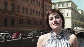 Жизнерадостная девушка в светлом платье поет вдоль реки в старом центре города видеоматериал