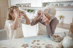 Жизнерадостная девушка и бабушка имея потеху с печеньями Стоковые Фото
