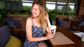 Жизнерадостная девушка сидя на кафе с коктеилем и lookin мороженого стоковое фото
