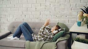 Жизнерадостная девушка слушает к наушникам музыки нося и moving оружиям и телу лежа на кресле дома самомоднейше видеоматериал