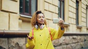 Жизнерадостная девушка смешанной гонки звонит видео-, говорит и смеется над держащ smartphone и смотрящ экран самомоднейше сток-видео
