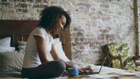 Жизнерадостная девушка смешанной гонки печатая на портативном компьютере для делить социальные средства массовой информации сидя  сток-видео