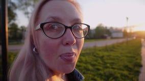 Жизнерадостная девушка смотрит камеру и игриво показывает ее право языка в камеру Смешная смешная рамка акции видеоматериалы
