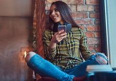 Жизнерадостная девушка студента брюнет в музыке вскользь одежд слушая пока использующ smartphone пока сидящ на силле окна Стоковая Фотография