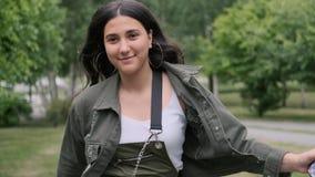 Жизнерадостная девушка хипстера в белых тапках скачет в парк слушая музыку используя портативный диктора видеоматериал