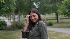 Жизнерадостная девушка хипстера идет и танцует в парке к музыке пока проводящ портативного диктора в ее руке : акции видеоматериалы