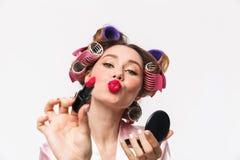 Жизнерадостная домохозяйка с curlers в робе волос нося стоковые фотографии rf