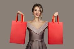Жизнерадостная женщина в платье вечера держа красные хозяйственные сумки стоковые изображения rf
