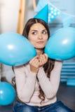 Жизнерадостная женщина держа 2 воздушного шара приближает к ее щекам Стоковая Фотография RF