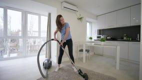 Жизнерадостная женщина домохозяйки делая очищая вакуумы и имеет танцы потехи и поет в комнате дома сток-видео