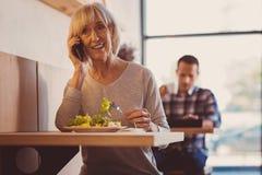 Жизнерадостная женщина звоня телефонный звонок пока ел вне Стоковая Фотография RF