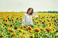 Жизнерадостная женщина на прогулке лета в поле с солнцецветами стоковая фотография