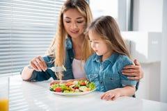 Жизнерадостная женщина подавая ее маленькая дочь здоровой едой Стоковые Изображения