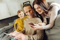 Жизнерадостная женщина показывая ее фото супруга на телефоне стоковое фото rf