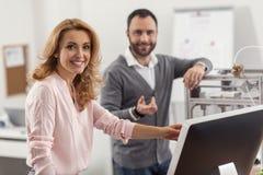 Жизнерадостная женщина представляя пока проверяющ коллег работает стоковое фото