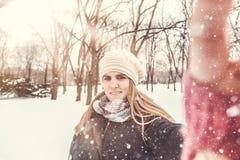 Жизнерадостная женщина принимая автопортрет путем использование ее умного телефона на снежный день стоковое изображение
