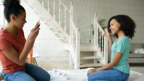 Жизнерадостная женщина смешанной гонки фотографируя его подругу используя камеру smartphone сидя на кровати в спальне дома Стоковые Изображения