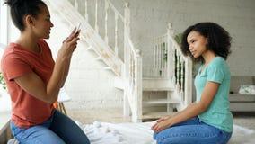 Жизнерадостная женщина смешанной гонки фотографируя его подругу используя камеру smartphone сидя на кровати в спальне дома Стоковая Фотография RF